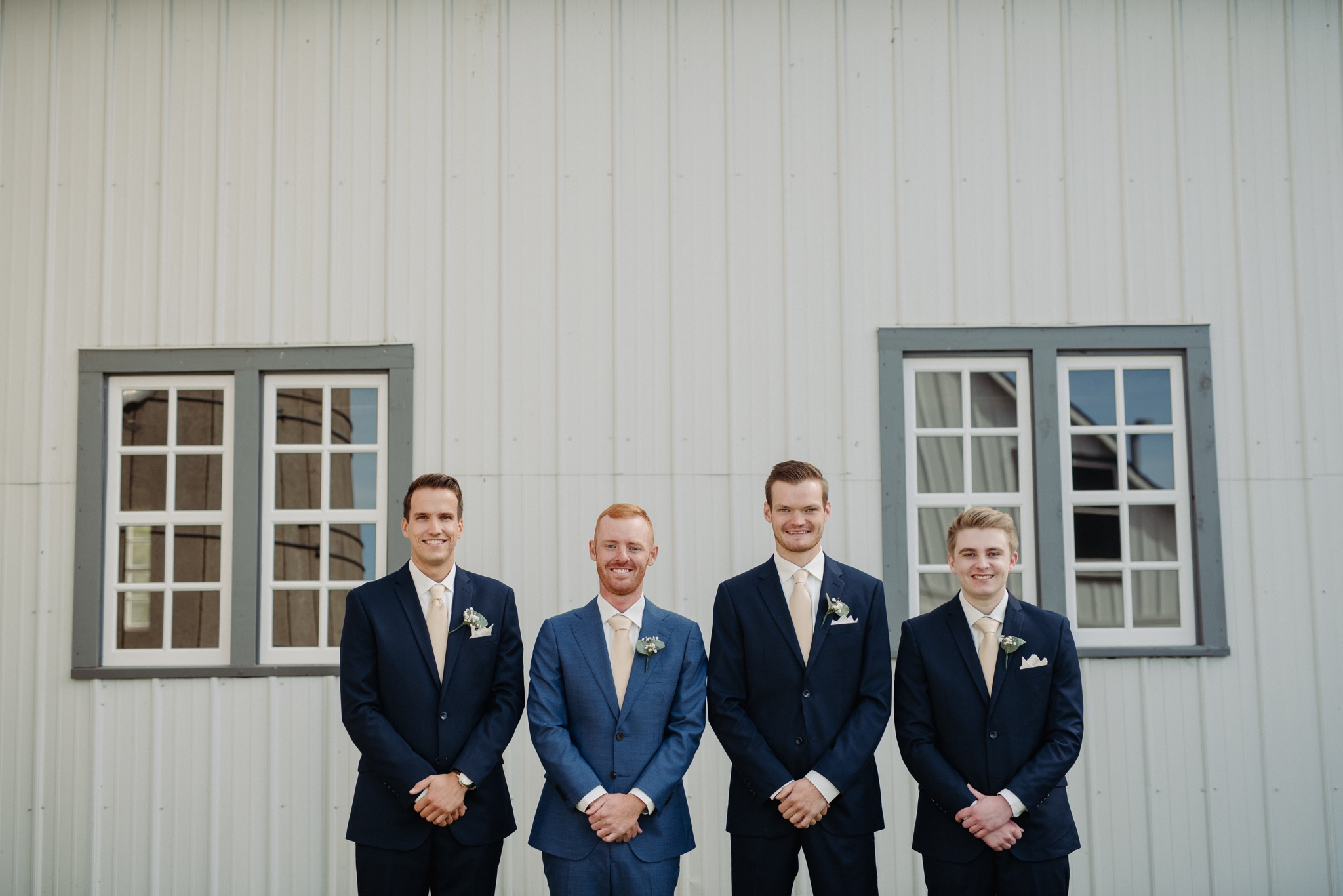 groom and groomsmen standing with hands folded