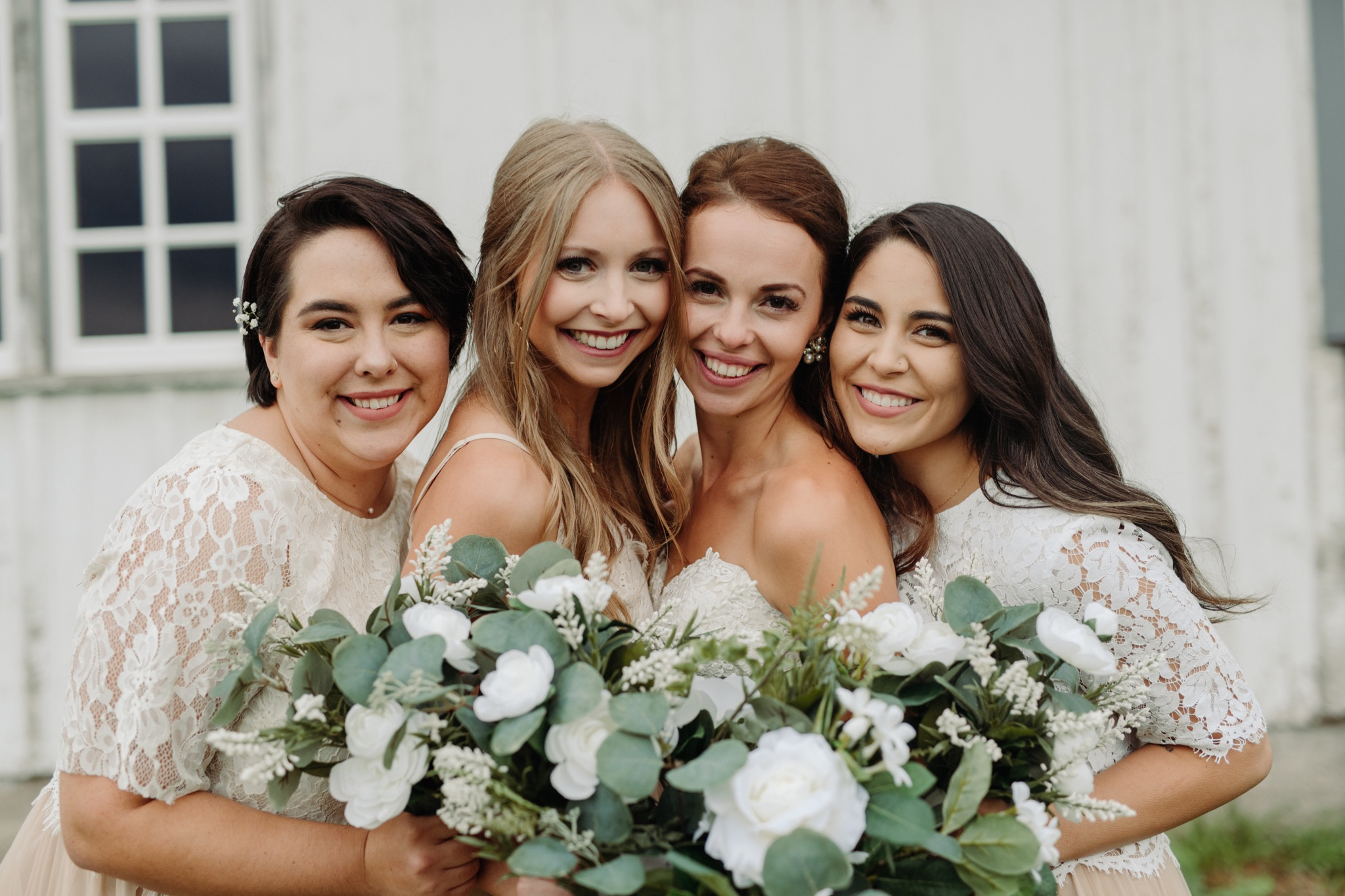bride standing with bridesmaids and holding flowers