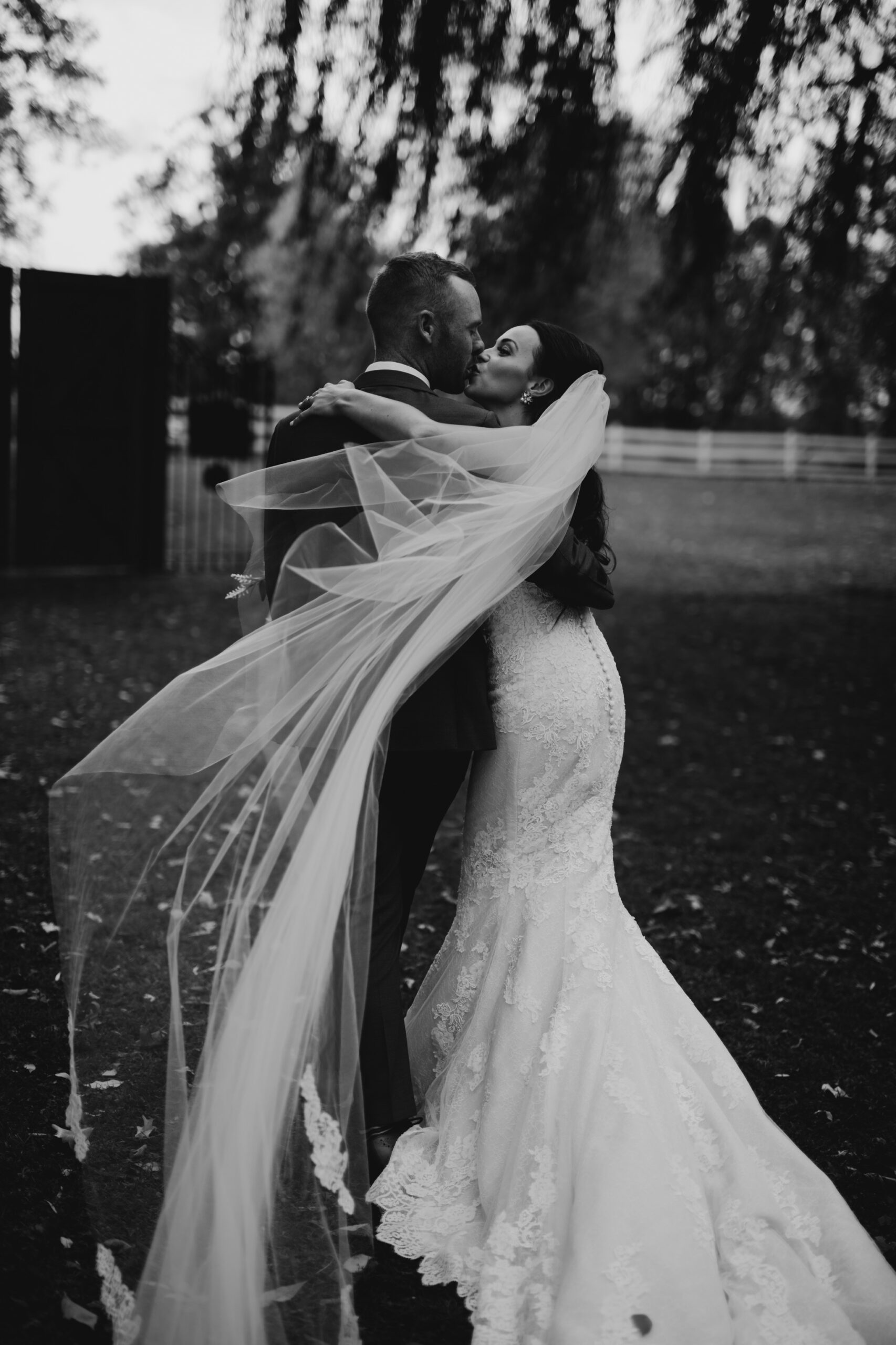 bride and groom kissing and bride's veil flying in the wind