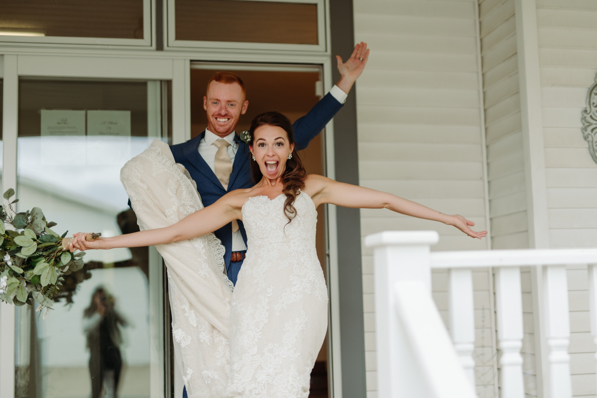 bride and groom smiling with arms open
