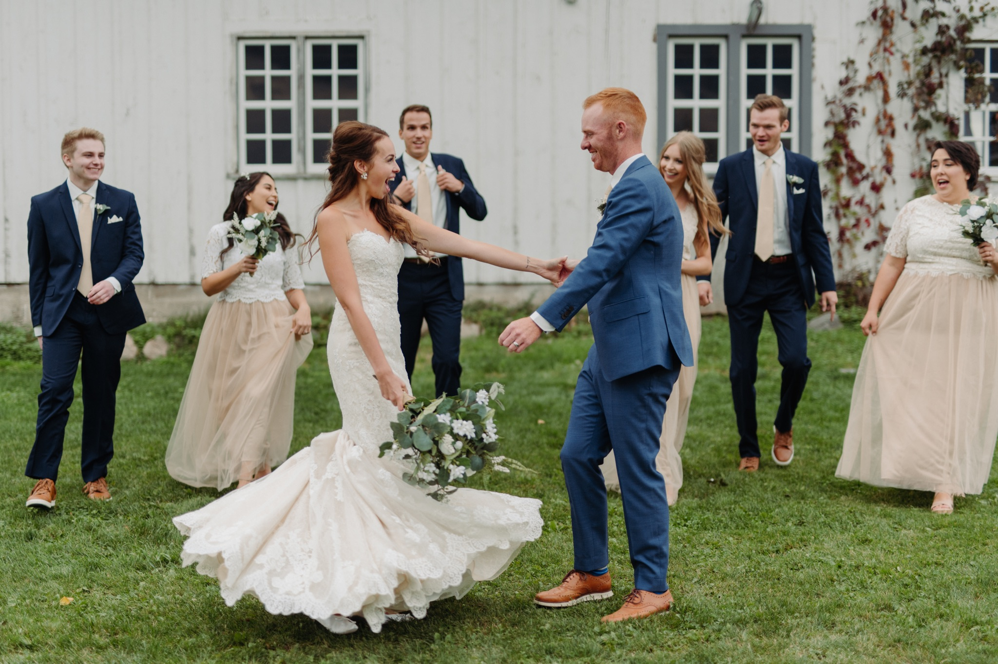 bride and groom dancing with wedding party behind them