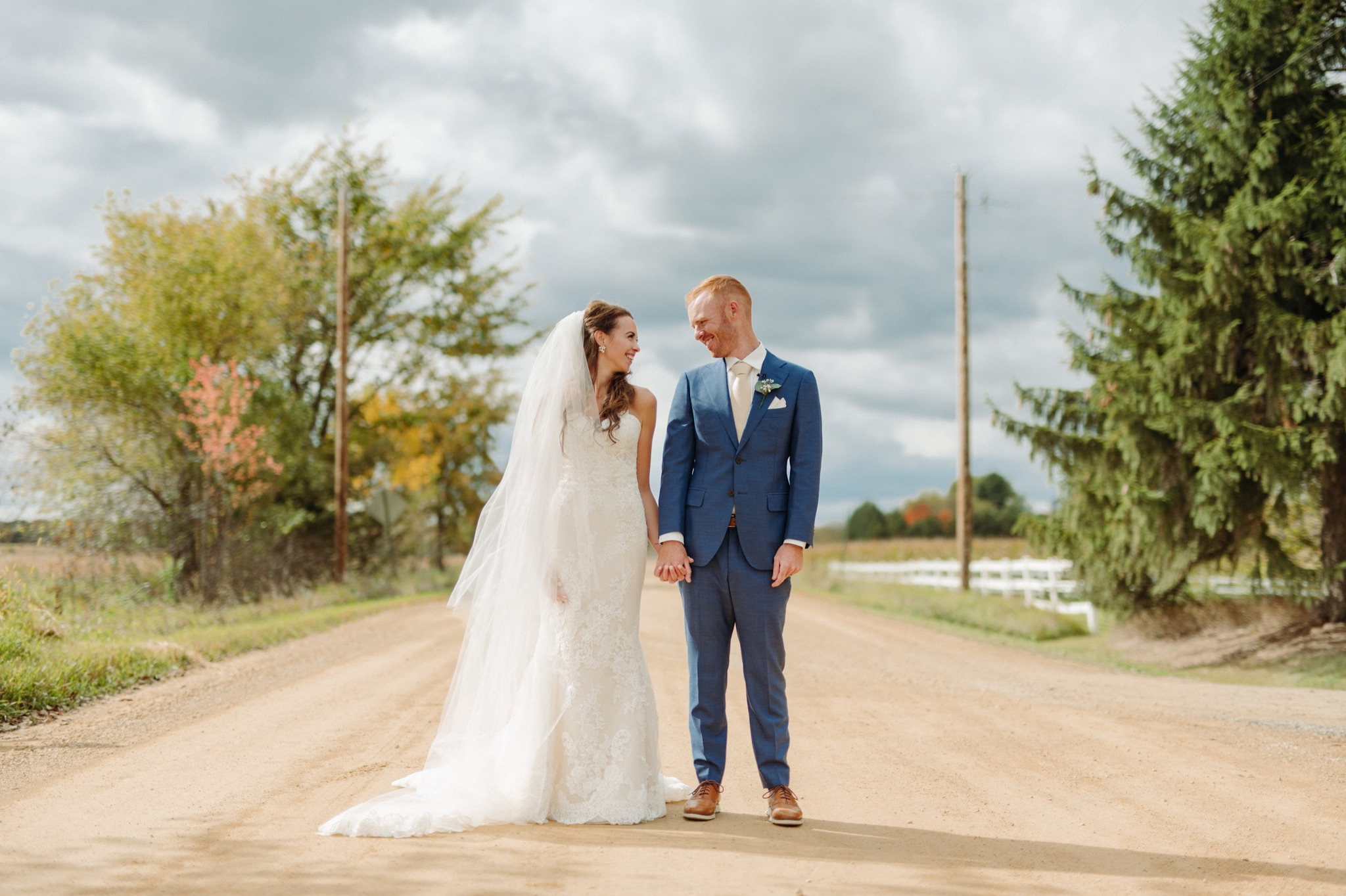 bride and groom holding hands and standing next to each other on a gravel road