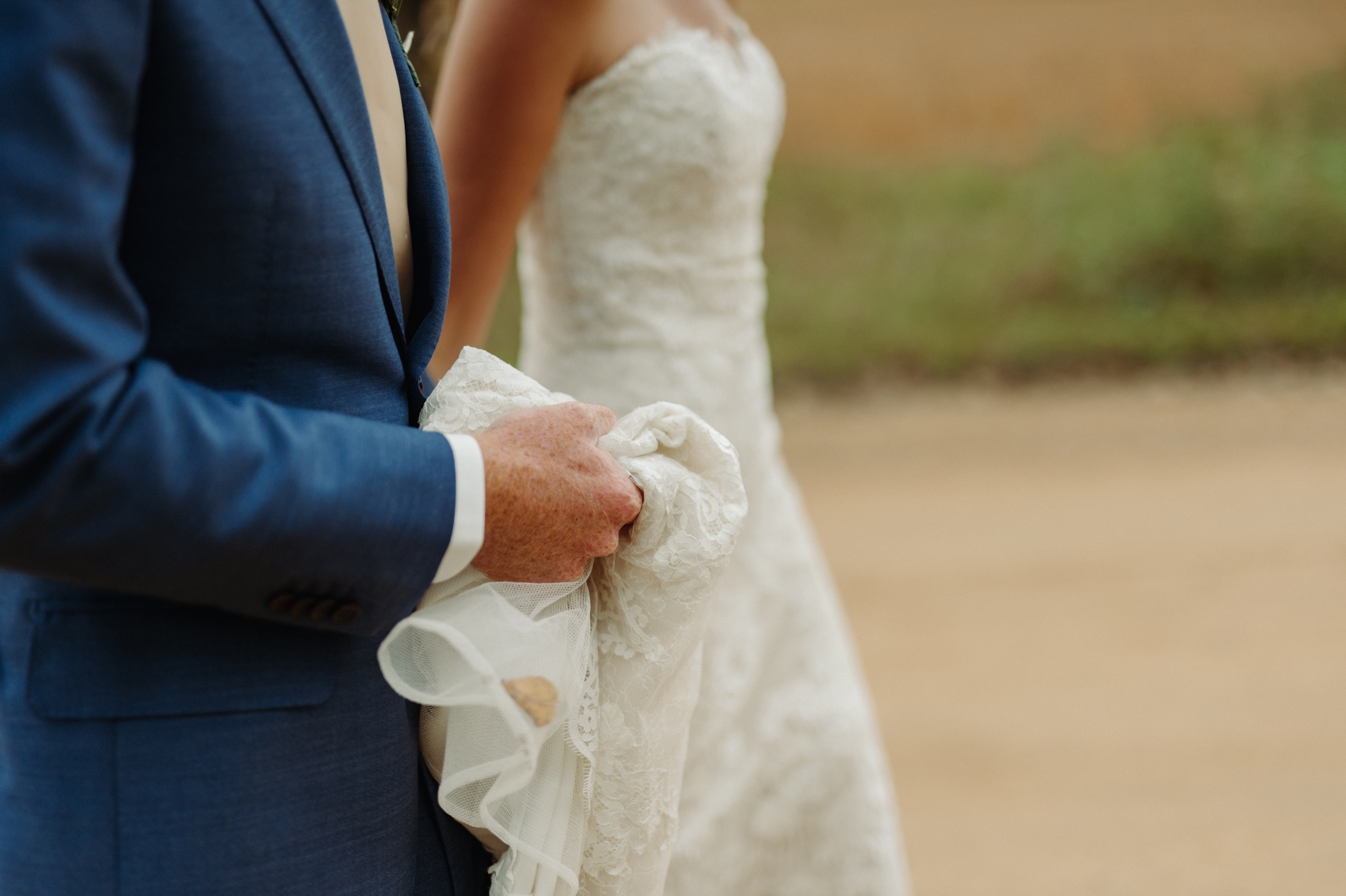 groom holding up bride's dress while walking next to each other