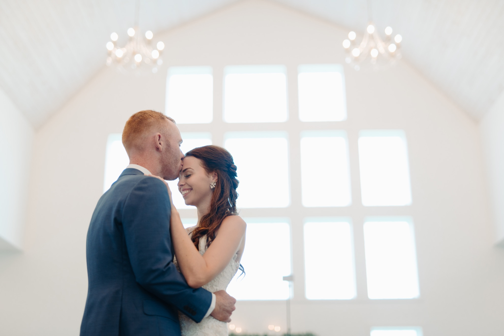 bride and groom dancing while groom kissing her forehead