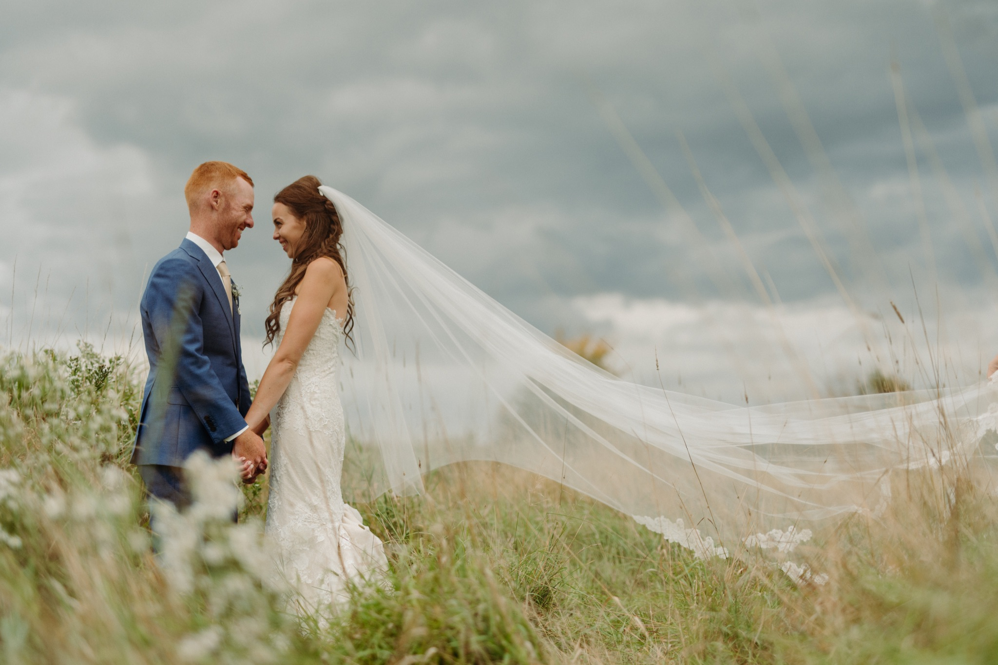 bride and groom standing in a field with bride's veil blowing in the wind