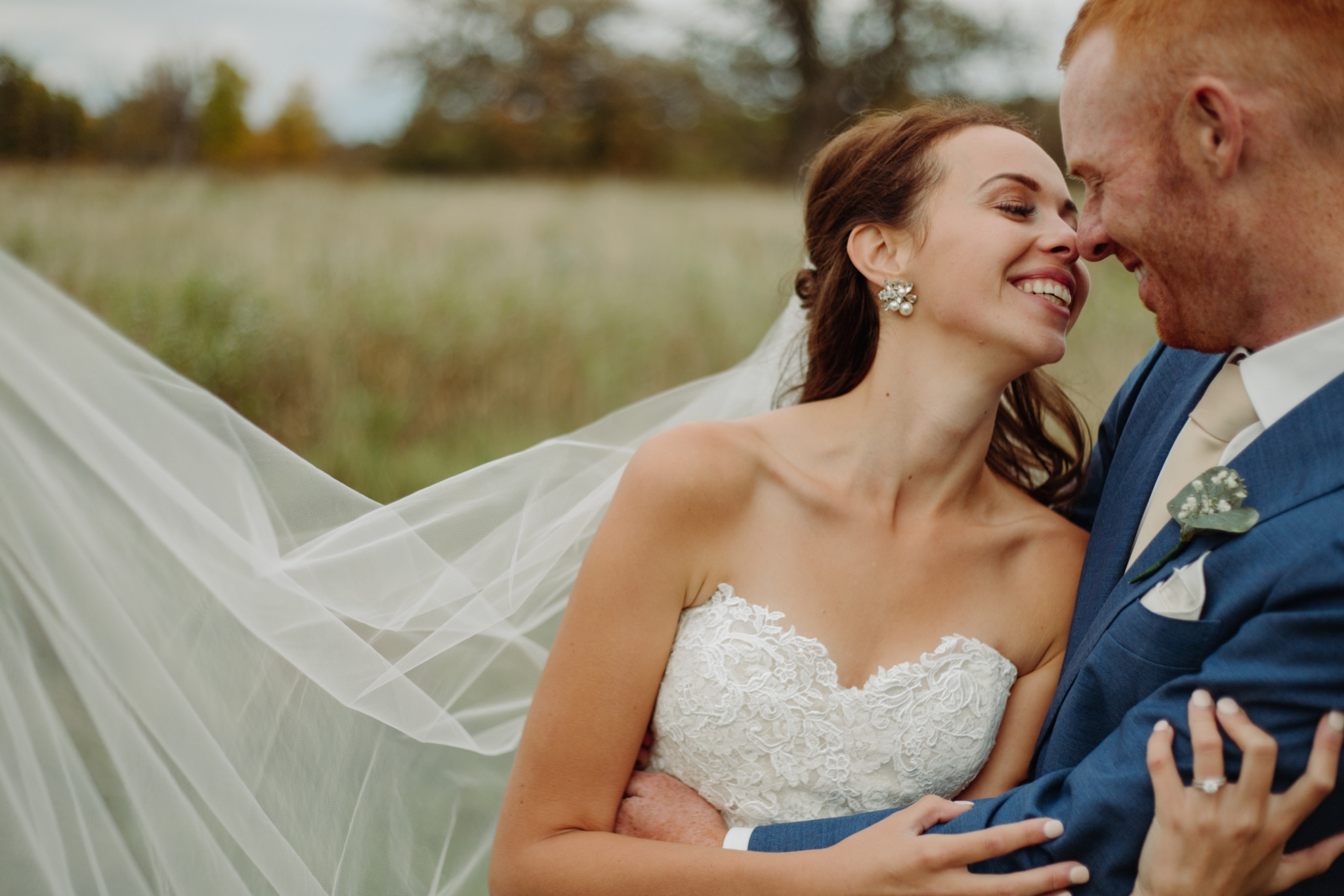 bride and groom smiling at each other and holding each other