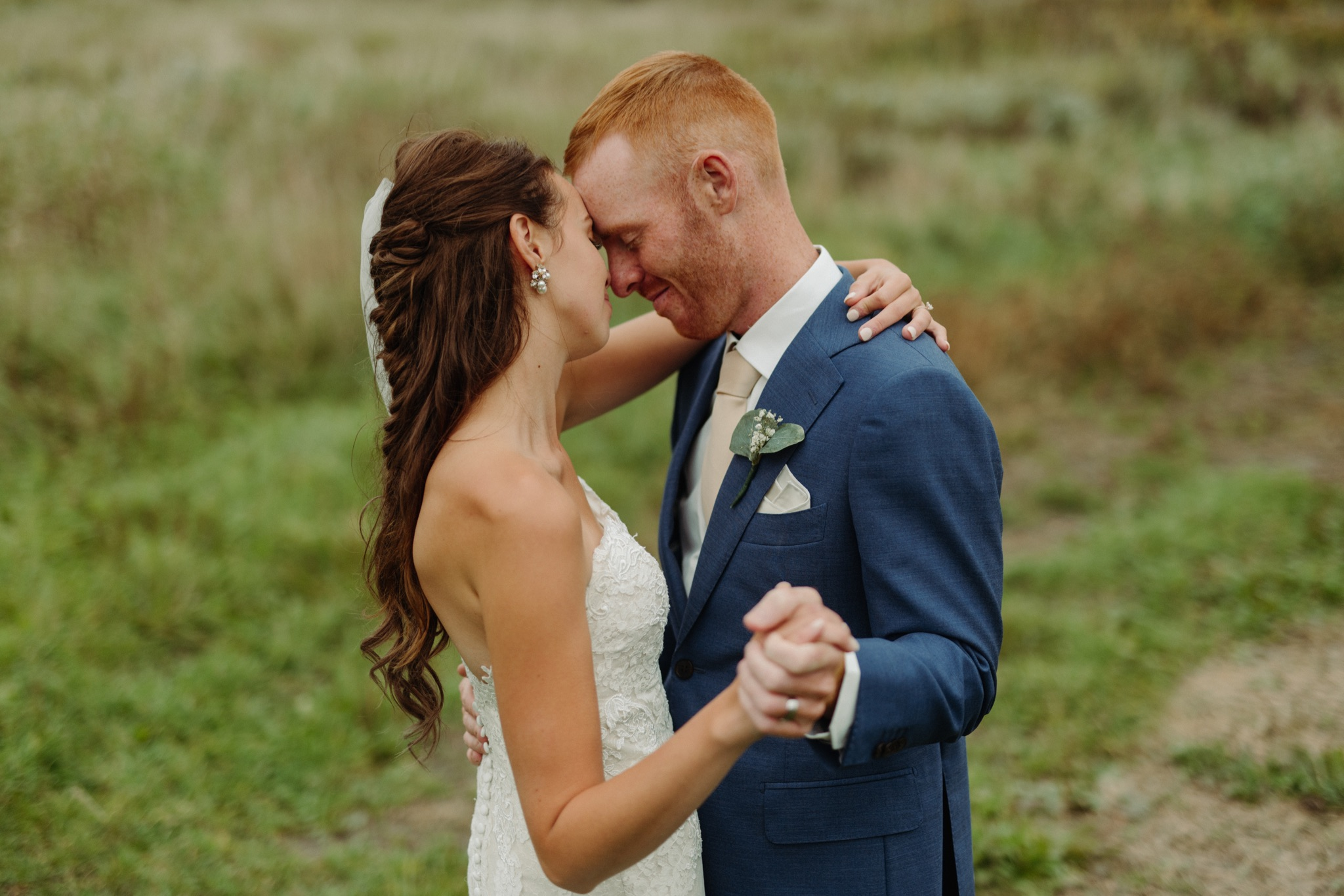 bride and groom slow dancing outside