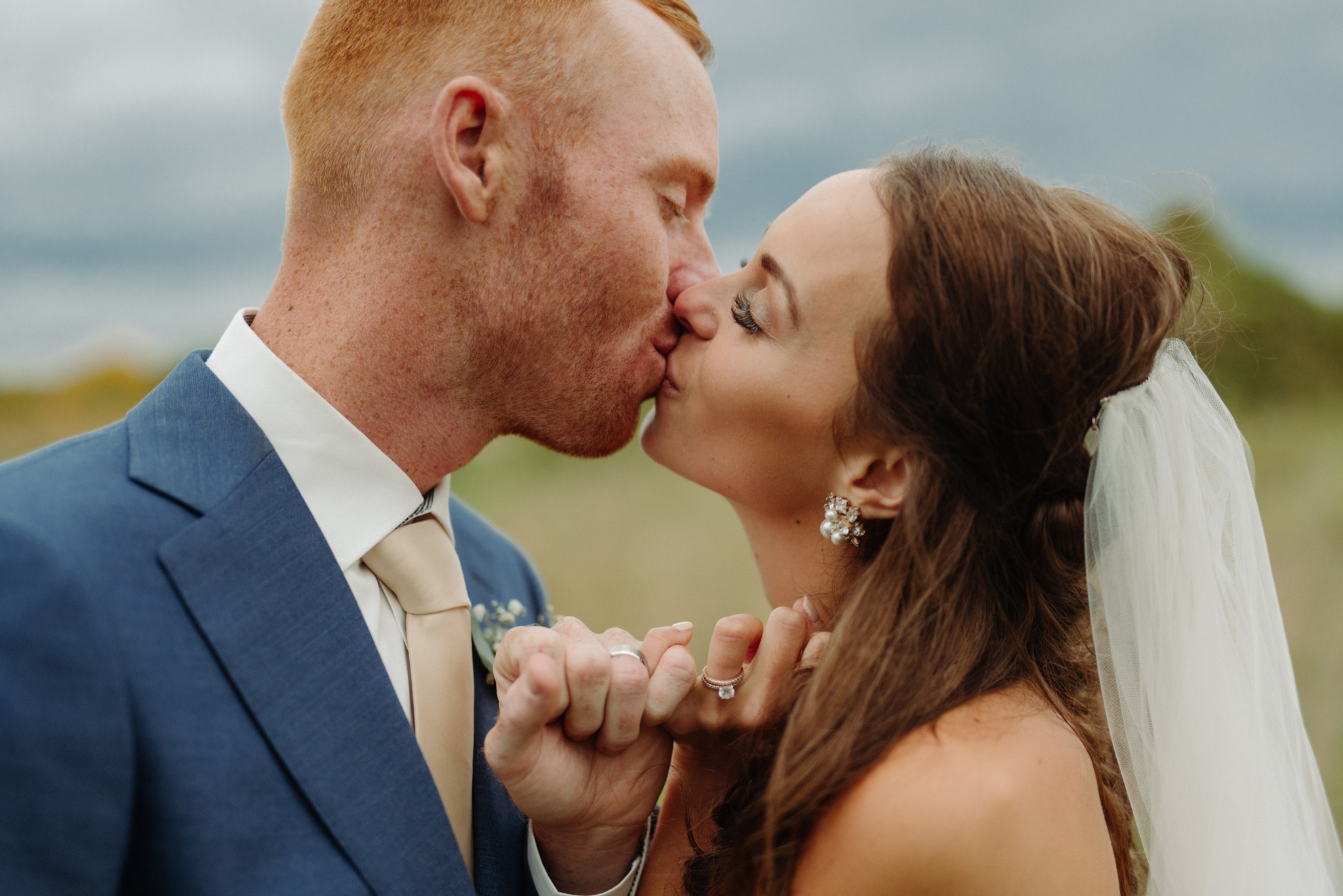 bride and groom kissing while crossing pinky fingers